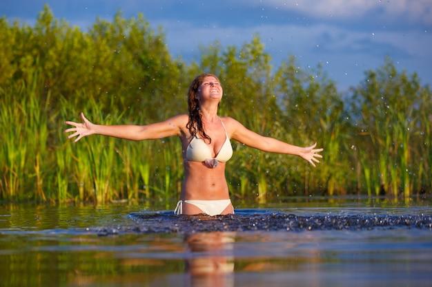 Beautiful young woman in a bikini bathing at the lake..