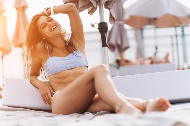 Beautiful young woman in bikini resting outdoors by the pool
