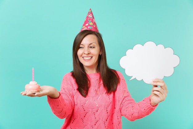 Beautiful young woman in birthday hat holding cake with candle, empty blank say cloud, speech bubble for promotional content isolated on blue background. people lifestyle concept. mock up copy space.