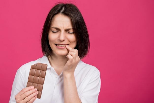 美しい若い女性はチョコレートのバーを噛み、歯痛を持っています