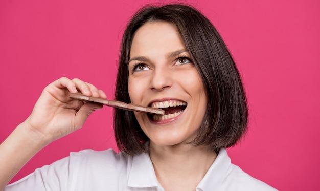 美しい若い女性がチョコレートのバーをかむ