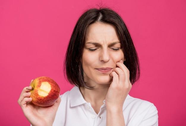 美しい若い女性は大きなリンゴを噛み、歯痛を持っています