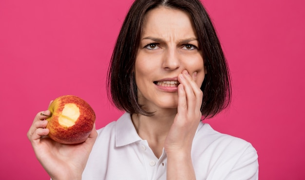 Beautiful young woman bites a big apple and has a toothache