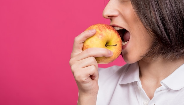Beautiful young woman bites a big apple