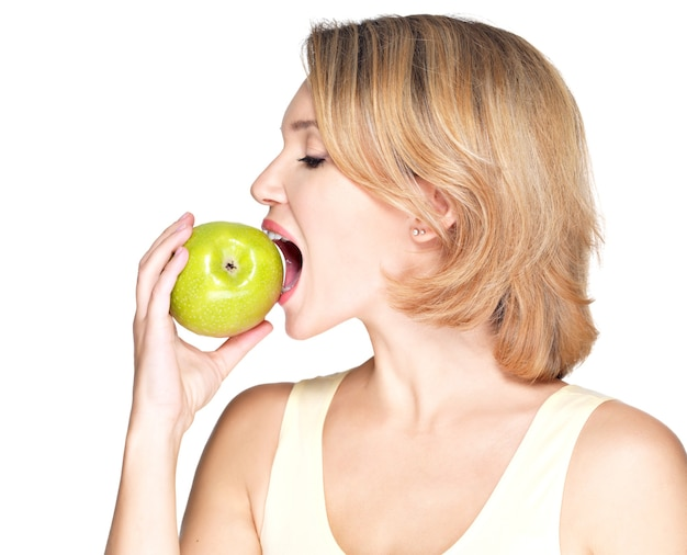 Beautiful young woman biting the biting a fresh ripe apple on white.