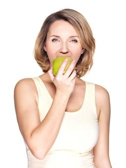 Bella giovane donna che morde il mordere una mela matura fresca su bianco.