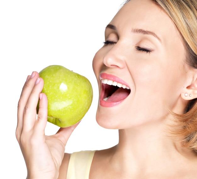 白で新鮮な熟したリンゴを噛んで噛む美しい若い女性。