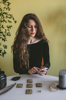 Beautiful young woman in a black corduroy dress is guessing on cards with runes