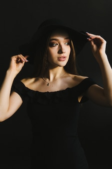Beautiful young woman in black dress and hat on black background