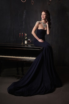 Beautiful young woman in black dress next to a piano with candelabra candles and wine, dark dramatic atmosphere of the castle. bohemia.