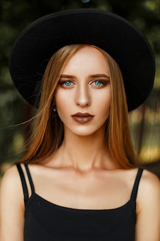 Beautiful young woman in black stylish clothes and a fashionable hat