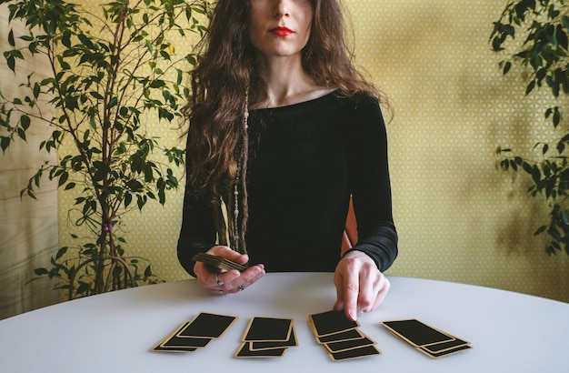 Beautiful young woman in a black velvet dress lays out cards on the table