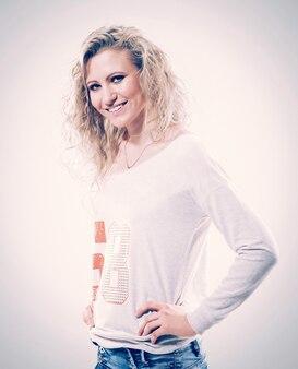 白いbackgのtシャツとジーンズで金髪の美しい若い女性