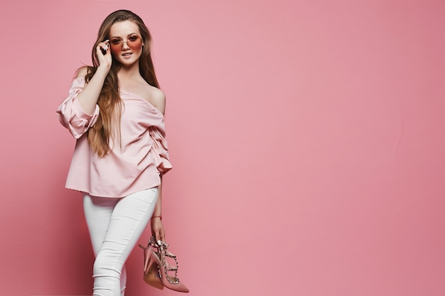 Beautiful young woman in a blouse with naked shoulders and fashionable sunglasses holding stylish shoes in hand and posing at pink background, isolated. copy space on the right for advertising