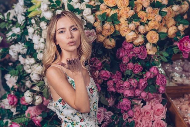 バラの背景に対して立っているキスを吹いている美しい若い女性