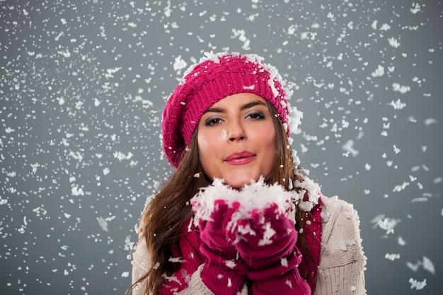 雪を吹く美しい若い女性