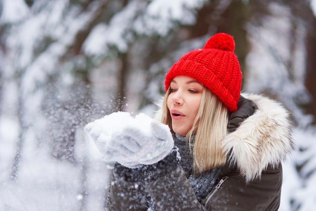 Bella giovane donna che soffia i fiocchi di neve