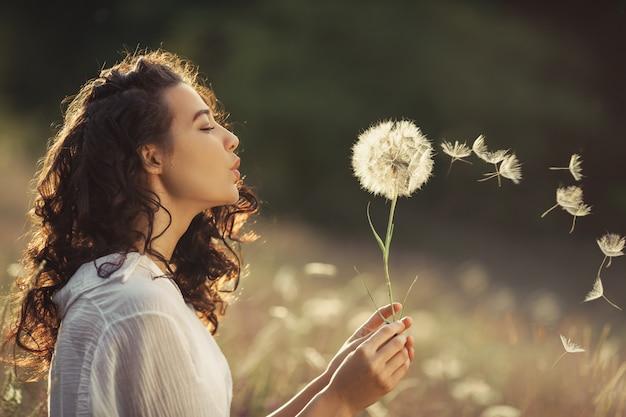 Красивая молодая женщина дует одуванчика в пшеничном поле в летний закат. концепция красоты лето