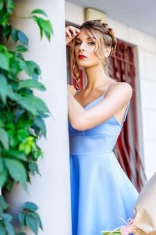 Beautiful young woman in a blue dress posing outside near a column