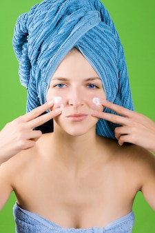 Beautiful young woman in blue towel applying facial cream on green background