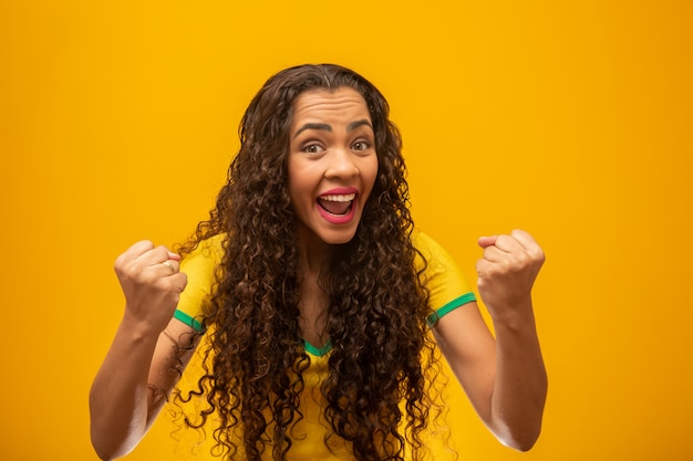 Beautiful young woman brazilian supporter with curly hair.