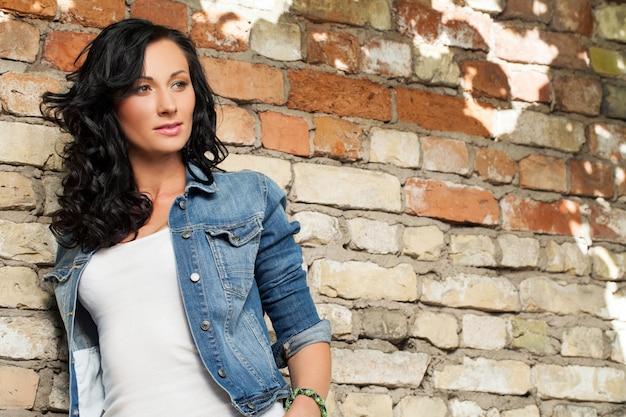 Beautiful young woman at the brick wall