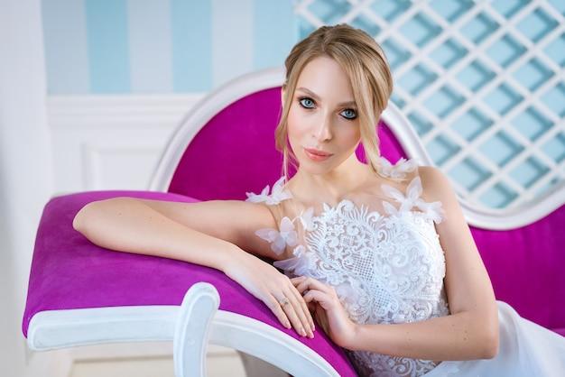 ブロンドの髪と化粧の美しい若い女性の花嫁。ソファに座って
