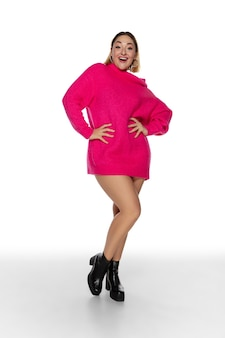 Bella giovane donna in maglione confortevole rosa brillante, manica lunga isolata su bianco
