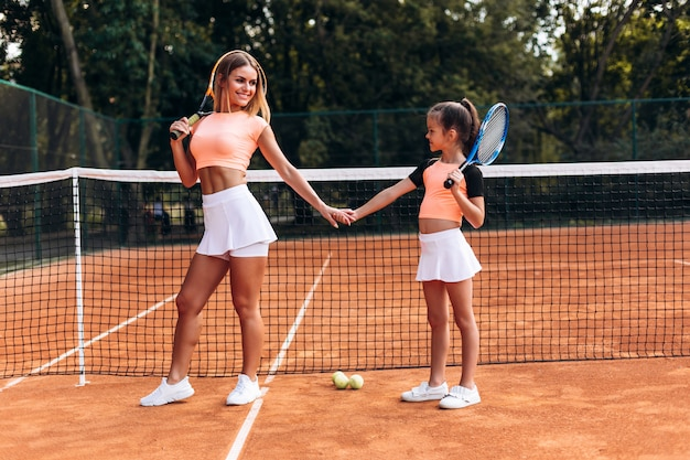 Beautiful young woman brought her daughter to the tennis court