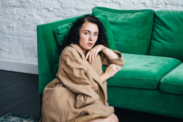 A beautiful young woman in a brown coat is sitting in a room on a green sofa. interior.