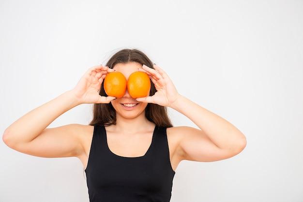 Красивая молодая брюнетка женщина держит апельсины перед глазами, здоровый завтрак или концепцию диеты