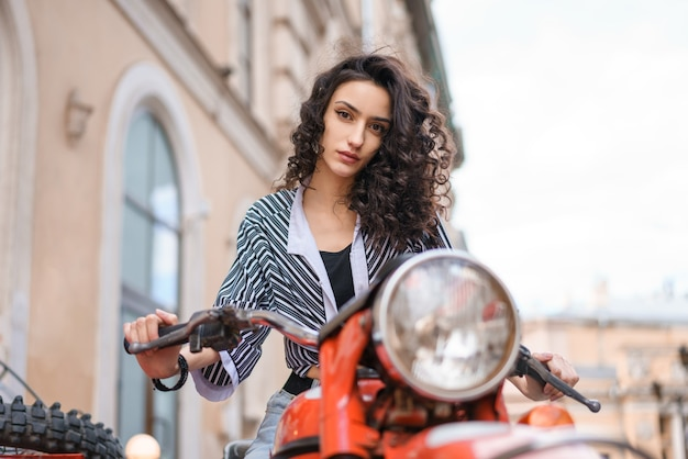Красивая молодая женщина брюнетка с вьющимися волосами, сидя на красном мотоцикле