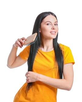 白い背景に対して髪をブラッシング美しい若い女性