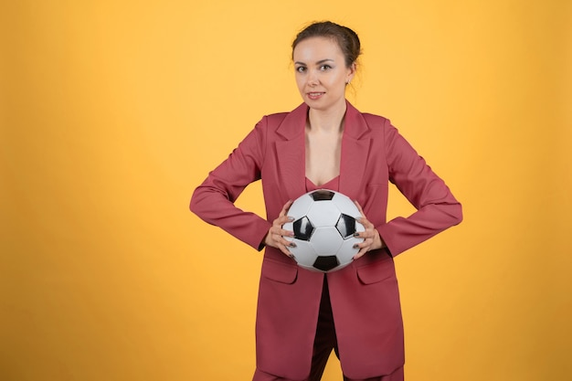 노란색 배경에 축구공 포즈를 취하는 아름다운 젊은 여성 사업가