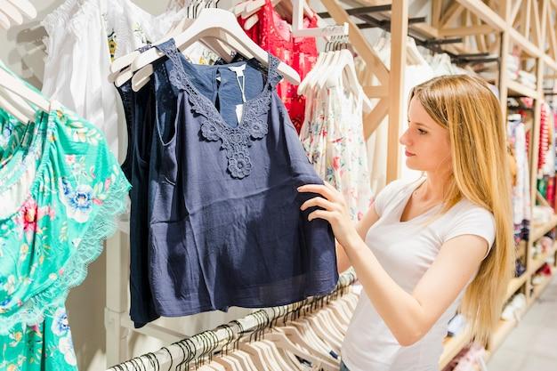 Bella giovane donna comprare vestiti nel negozio