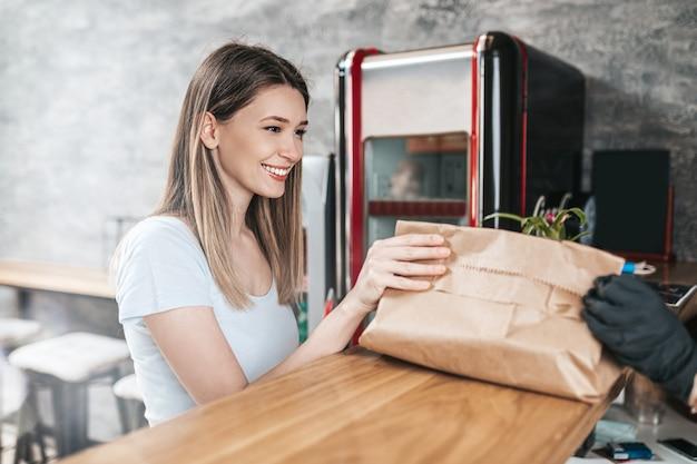 Красивая молодая женщина покупая еду в ресторане быстрого питания.