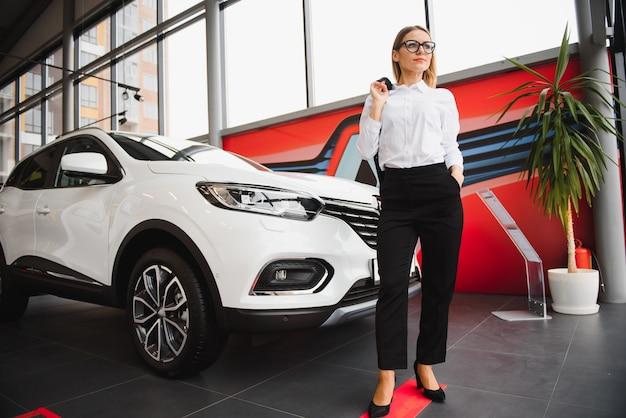 美しい若い女性がディーラーサロンで車を買う