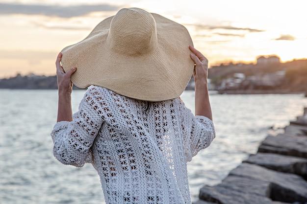 석양 바다로 아름 다운 젊은 여자. 긴 치마와 모자를 입고.