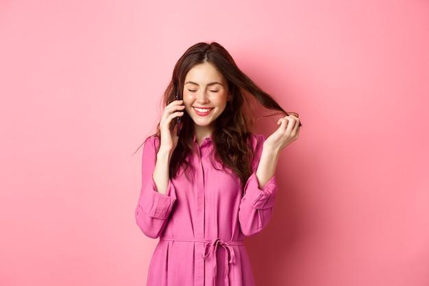Красивая молодая женщина звонит кому-то, смеется и улыбается во время телефонного звонка, разговаривает с другом и играет с прядями волос, стоя у розовой стены.