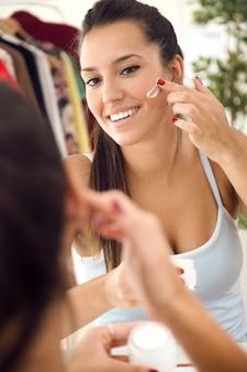 Bella giovane donna che si prende cura della sua pelle vicino allo specchio in bagno.