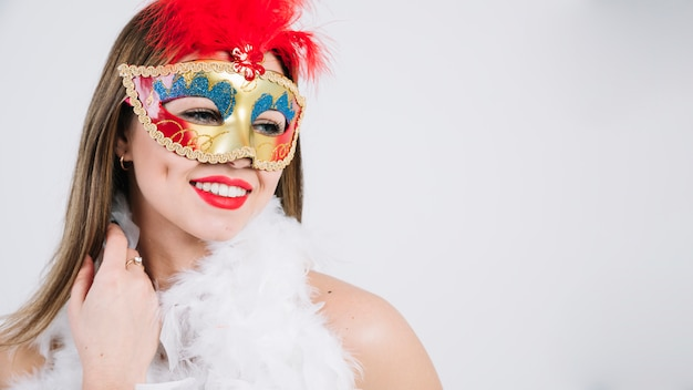Beautiful young woman in carnival mask and feather boa on white background