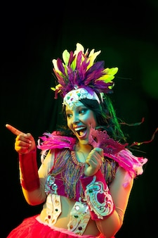 Beautiful young woman in carnival mask and masquerade costume in colorful lights