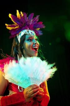Bella giovane donna in maschera di carnevale e costume in maschera alla moda con ventaglio di piume in luci colorate e bagliore su sfondo nero.