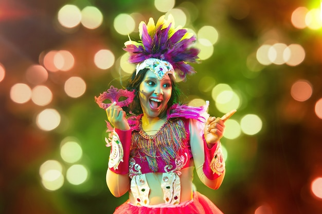 Beautiful young woman in carnival mask and stylish masquerade costume with feathers and sparklers in colorful bokeh on black background