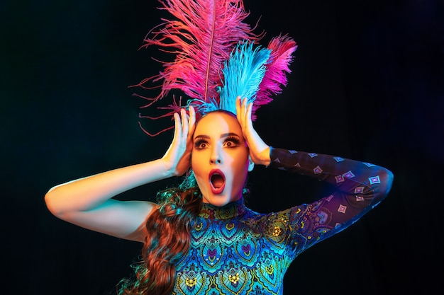 Beautiful young woman in carnival and masquerade costume in colorful neon lights on black wall