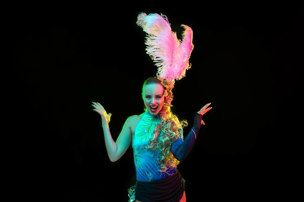 Beautiful young woman in carnival and masquerade costume in colorful neon lights on black