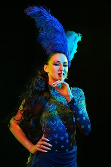 Beautiful young woman in carnival, stylish masquerade costume with feathers on black background in neon light.