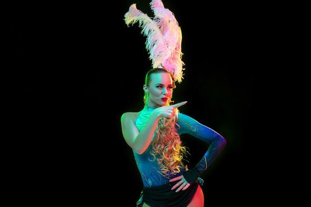 Bella giovane donna in carnevale, elegante costume in maschera con piume su sfondo nero in luce al neon.
