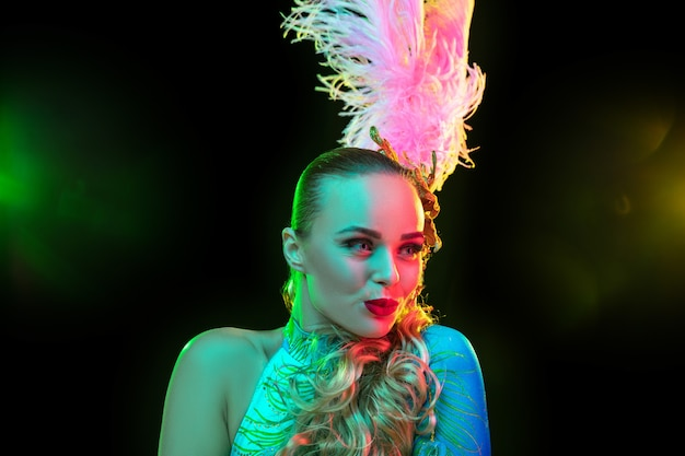Beautiful young woman in carnival, stylish masquerade costume with feathers on black wall in neon light