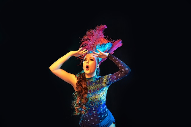 Bella giovane donna in carnevale, elegante costume in maschera con piume sul muro nero in neon